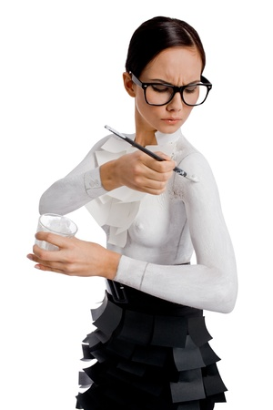 bodypaint: Image of pretty woman in eyeglasses painting her shoulder in white color with special brush Stock Photo