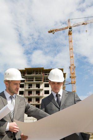 Portrait of confident colleagues looking at new construction plan and brainstorming Stock Photo - 8434871