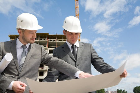 Portrait of confident partners looking at new construction plan and discussing it Stock Photo - 8434696