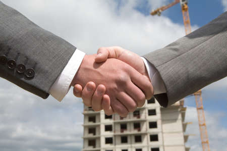 ovation: Photo of handshake of business partners after striking deal on background of building under construction