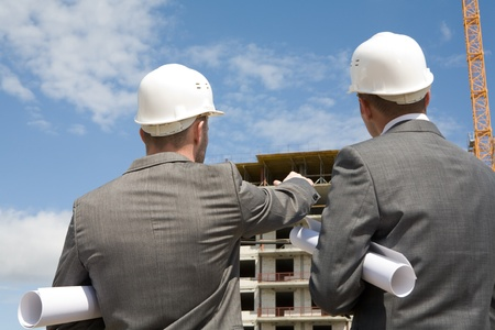 Rear view of workers interacting and looking at building Stock Photo - 8435289