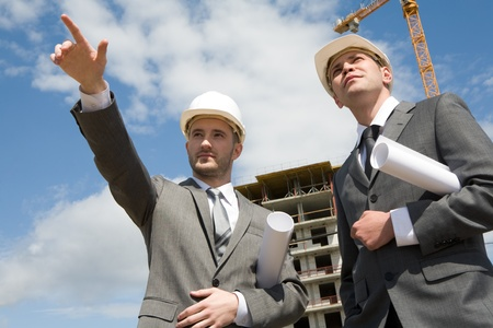 Photo of young engineer showing something to his colleague during meeting at building site Stock Photo - 8435043