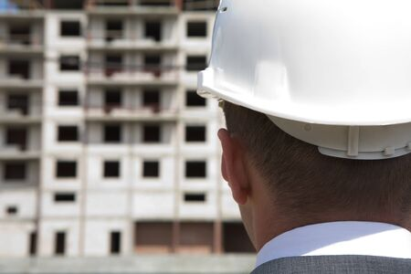 Close-up of builder head wearing white helmet with building under construction at background  photo