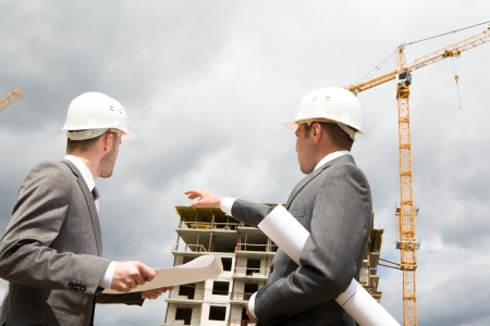 Photo of young engineer showing something to his partner at building site Stock Photo - 8434545