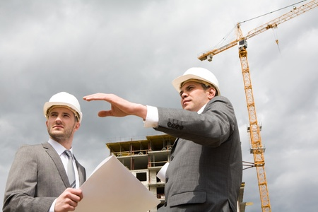 Photo of confident engineer showing something to his partner at building site Stock Photo - 8434570