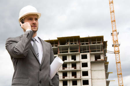 Portrait of confident foreman calling by mobile phone at building site  Stock Photo - 8434877