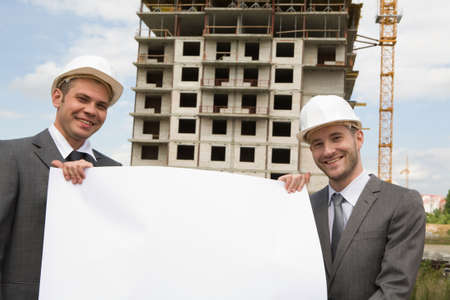 Portrait of two successful builders holding large sheet of paper with construction at background Stock Photo - 8434517