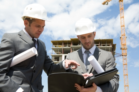 cantieri edili: Ritratto di due costruttori piedi al cantiere e discutere il nuovo progetto detenuta da uno di loro