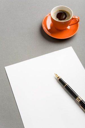 Image of blank paper sheet with fountain pen and red cup of coffee near by photo