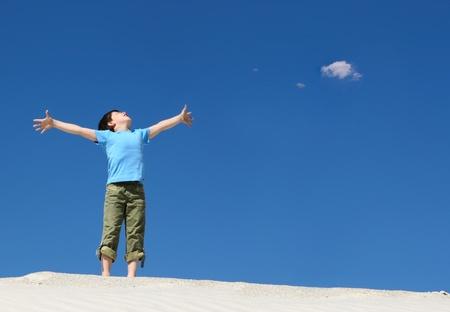 gratitudine: Immagine del ragazzo gioioso in abiti casual, in piedi sulla sabbia con le braccia aperte