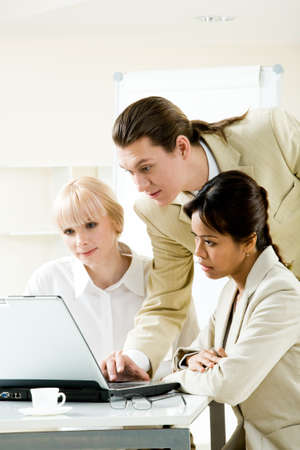 Photo of successful businesspeople looking at laptop display in office photo