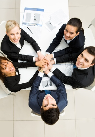 looking upwards: Above view of business people with their hands on top of each other and looking upwards