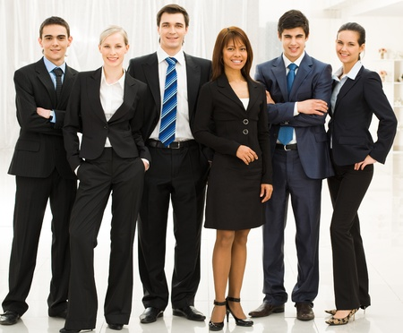 Portrait of confident business group standing in row and looking at camera  photo