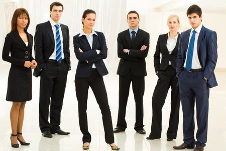 specialists: Portrait of confident well-dressed business people standing in semicircle with smart lady in center