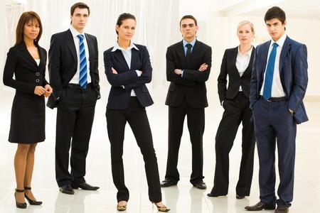 especialistas: Retrato de personas de negocios bien vestido conf�a en pie en semic�rculo con dama inteligente en centro