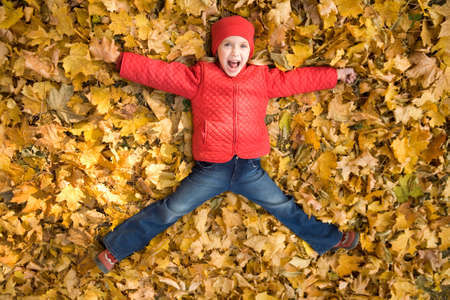 Above view of excited child shouting from happiness while lying on dry autumnal leaves photo