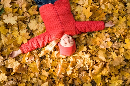 Above view of peaceful child enjoying herself while lying on autumnal ground photo