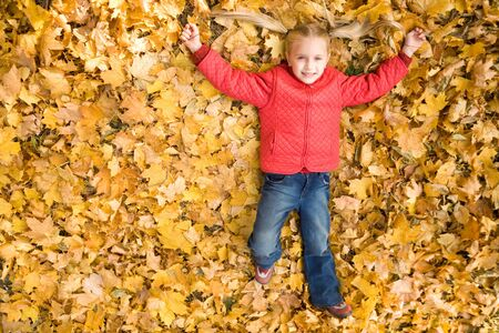 Above view of smiling girl enjoying herself while lying on autumnal ground