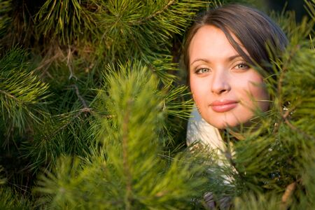 Pretty woman smiling and looking at camera out of pine tree branches    photo