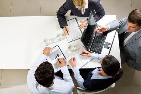 company job: Image of company of successful partners discussing contract at meeting