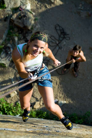 rockclimb: Image of woman hanging on the rope and man standing by her Stock Photo