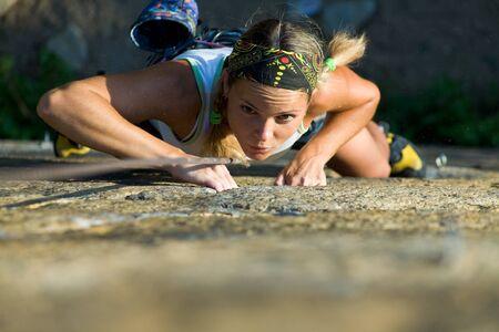 rockclimb: Attractive girl climbs a granite rock Stock Photo