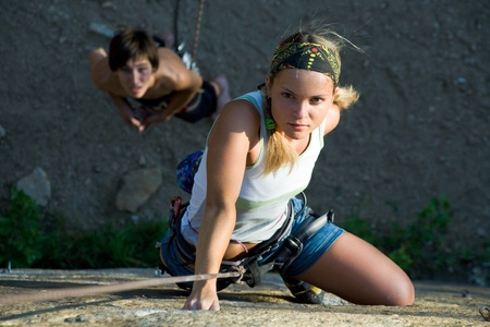 rapelling: Woman and man engage in extreme sports
