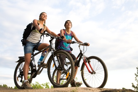 Image of sporty couple on bicycles outdoors against cloudy sky