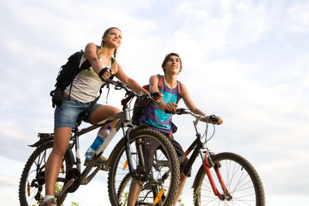 somewhere: Image of sporty couple on bicycles outdoors looking somewhere with smiles