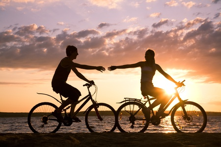 bicycle silhouette: Silhouettes of happy couple stretching arms to each other while riding bicycles on seashore at sunset Stock Photo