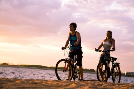 Figures of happy couple standing on seashore with their bicycles and enjoying sunset photo