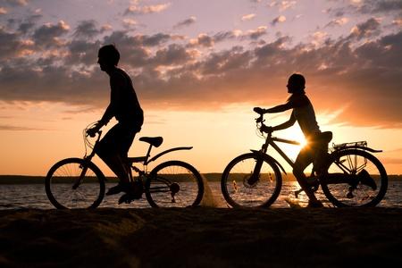 Silhouettes of couple riding their bicycles on seashore at sunset photo