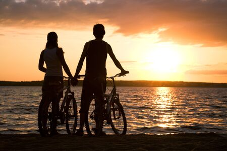 Rear view of couple standing on seashore with their bicycles and enjoying sunset Stock Photo - 8447428
