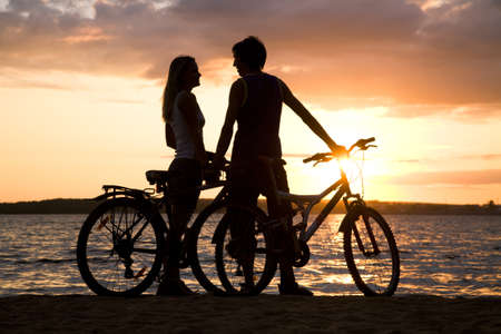 Young couple standing on seashore with their bicycles and looking at each other photo