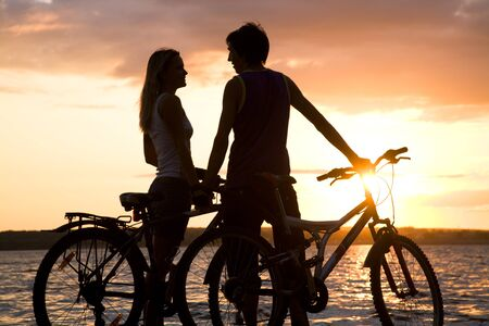 Young couple by lake with their bicycles and looking at each other in the evening photo