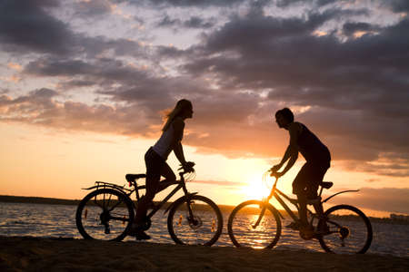 Silhouettes of couple opposite each other on their bicycles by the sea at sunset Stock Photo - 8447448