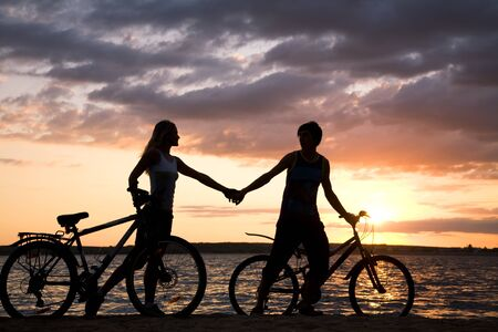 Silhouettes of couple holding each other by hands while walking down seashore with their bicycles at sunset photo