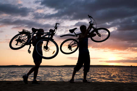 Silhouettes of couple carrying their bikes while walking down seashore at sunset photo