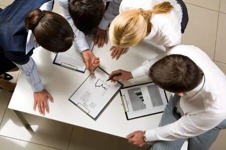 team strategy: Above view of friendly workteam discussing business-plan  Stock Photo