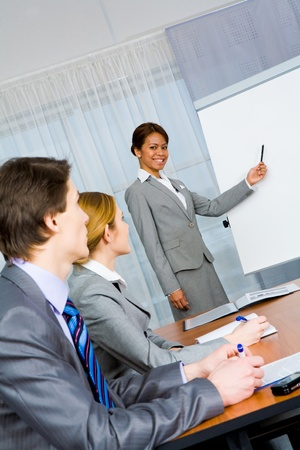 resourse: Photo of confident employees listening to smart teacher presenting new project Stock Photo