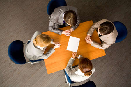 Above view of business people around workplace with blank paper in center photo