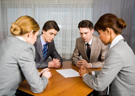 Portrait of business people sitting around table and looking at blank paper in center photo