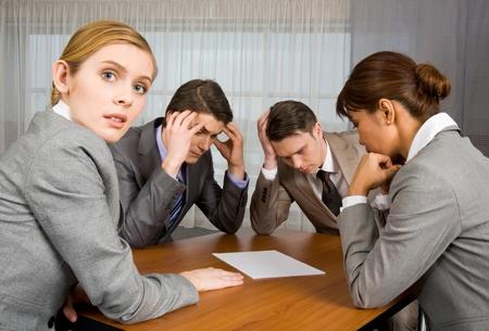 hombre preocupado: Retrato de gente de negocios sentados alrededor de mesa y de intercambio de ideas mientras una mujer mirando c�mara