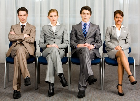 people in a row: Portrait of confident business group sitting in row and looking at camera  Stock Photo