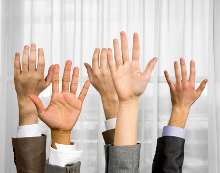 simultaneously: Close-up of several human hands raised simultaneously