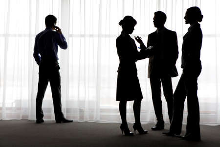 Four outlines of business partners communicating with calling male near by photo