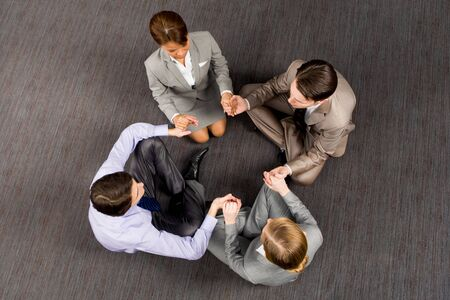 Above view of thoughtful business people sitting on the floor with their legs crossed and holding each other by hands photo