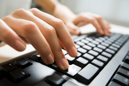 Image of female fingers pushing enter key during computer work photo