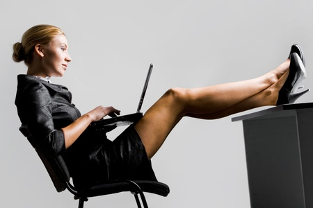 Profile of serious businesswoman typing on laptop over grey background photo