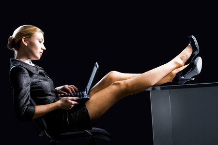 Profile of pretty businesswoman typing on laptop with her legs on table Stock Photo - 8441277